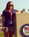 Callie Bartel standing next to an Olympic podium