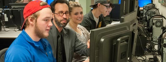 CIS students working with the prfessor in a computer lab
