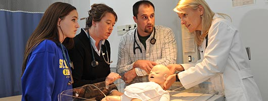 Nursing professional teaching students within the SIM lab