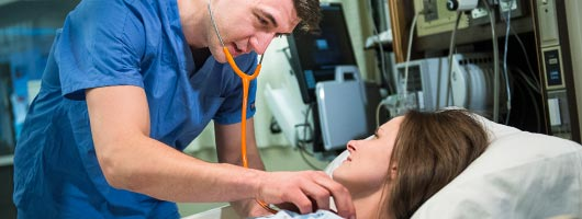 Nursing student in a clinical setting listening to a patient's heartbeat