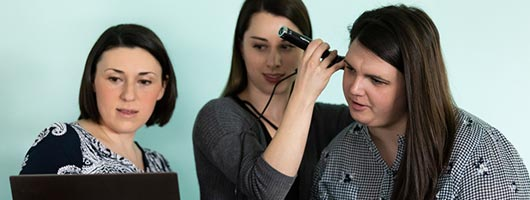 Instructor teaching students how to use an ear inspection device in a lab setting