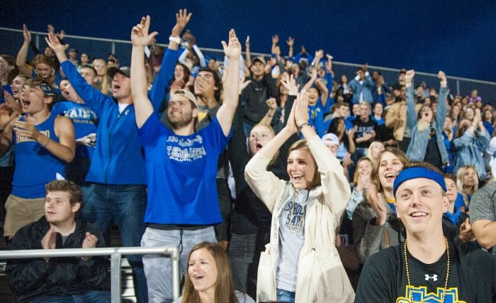 Group of St. Scholastica Saints students enjoying a football game