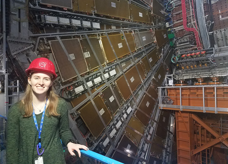 Megan Schiferl next to the ATLAS experiment