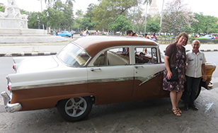 Lynne Hamre, dean of the School of Business, with Julio Alvarez, owner of Nostalgiccarcuba.com.