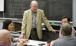 Bob Hartl, associate management professor, works with a masters-level class.