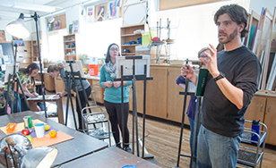 Paul LaJeunesse works with students during an art class.