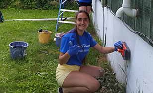 Russian exchange student Rita Bekirova preps a West Duluth house for painting.