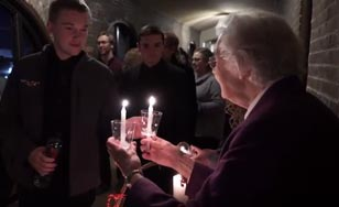 Sister handing out candles to students after Advent Vespers.