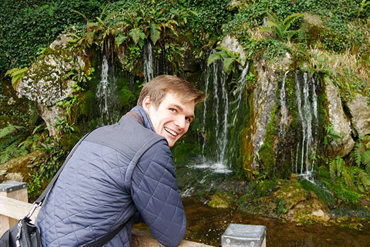 Charley Hagen standing near a waterfall while on a study abroad trip in Ireland