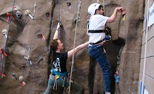Annalisa Dietz (left) assists Courage Kenny participant Joe Kent as he scales the BWC climbing wall.