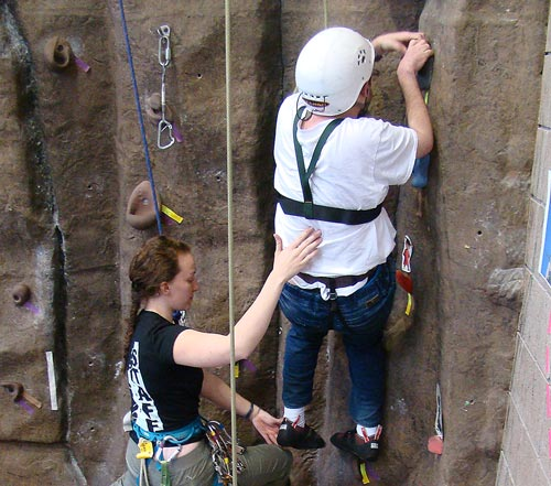 Annalisa assists Courage Kenny participant Joe Kent as he scales the climbing wall.