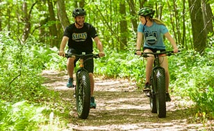 Two students biking on the trails of the CSS Duluth campus.