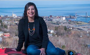 Alicia Cyr sitting on a hillside overlooking downtown Duluth, MN