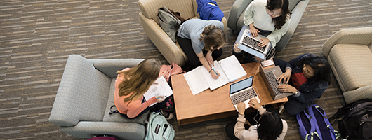 Top down view of 4 students studying in the Science Building's Benedictine Commons