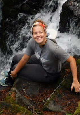 Aleah sitting next to waterfall