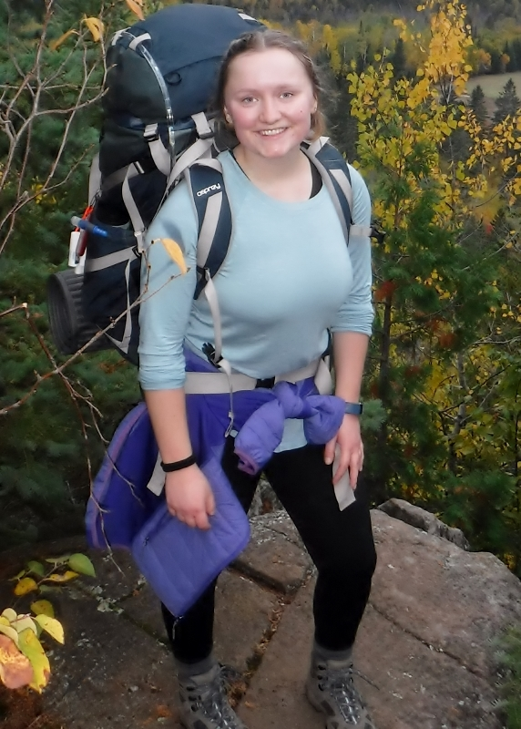 Amelia wearing backpack on rock overlook