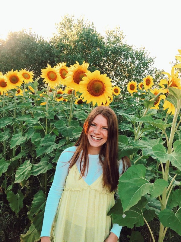 Emily in front of sunflowers