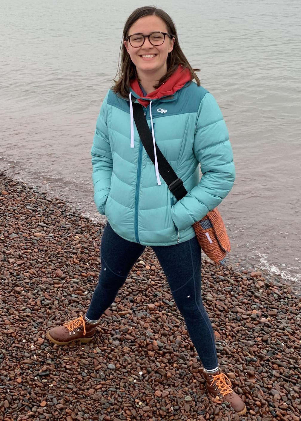 Maddie posing on a rock beach