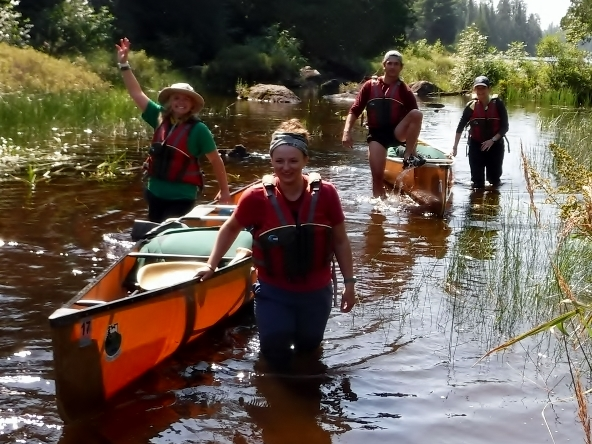 Group pulling canoe through narrow river
