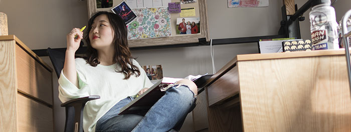 Student sitting in her room in Somers Hall at St. Scholastica.
