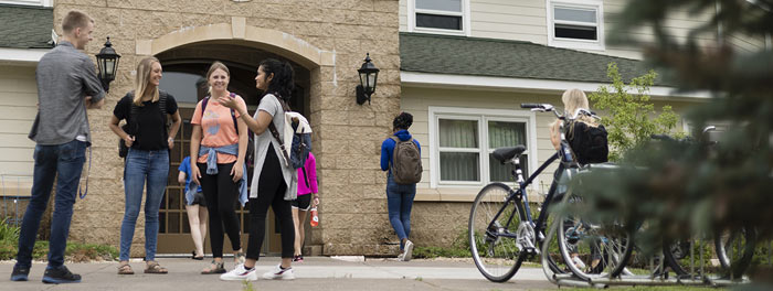 Students visiting in front of the upper-class housing at St. Scholastica.