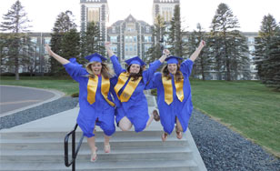 Graduates leaping off stairs in front of Tower Hall