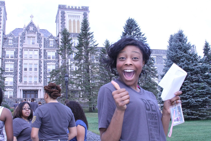 Student giving thumbs up in front of tower hall