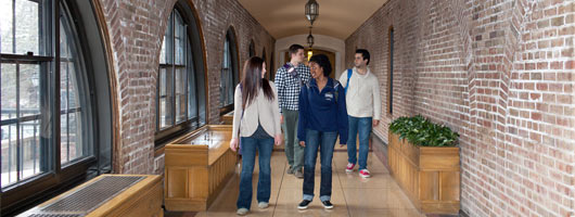 Group of students walking through chapel hallway towards Tower Hall