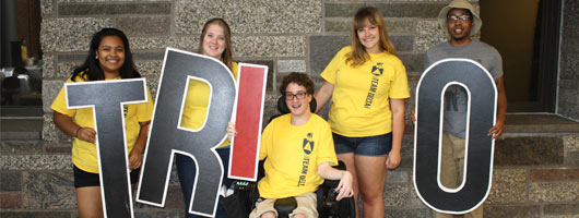 Five TRIO students holding TRIO letter signs