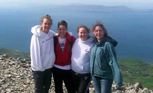 Four female students standing along ocean shore Croagh Patrick, Ireland