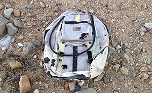A worn backpack left behind by a migrant in the desert and found by students during their walk with Shura of Green Valley Samaritans.