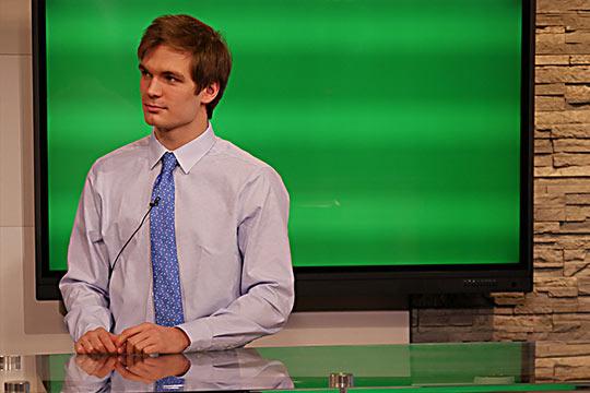 Charley Hagen sitting behind the anchor desk at WDIO