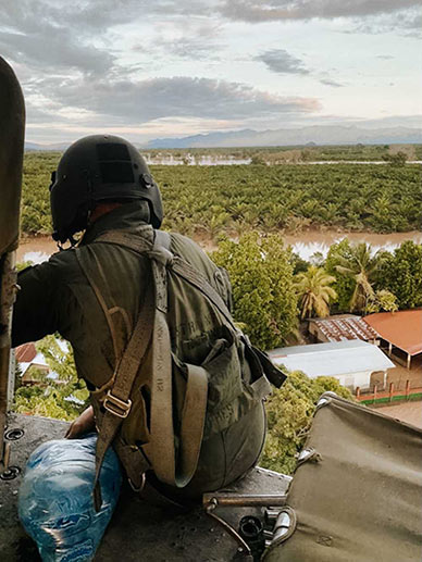 A member of the Honduran Air Force looks out over the flooded landscape during a supply delivery.
