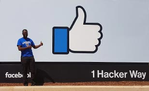 Malvern Madondo standing in front of the Facebook sign during his internship