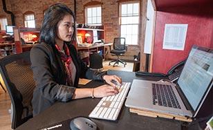 Zhara Davies working on her computer at HTK Marketing