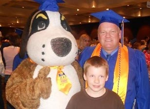 Don and Nick Claveau posing with mascot, Storm at the 2012 CSS Graduation Ceremony.