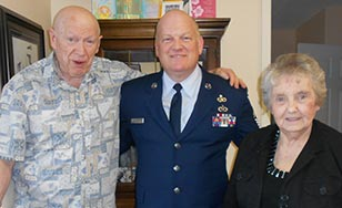 Don Claveau wearing his veterans uniform as he poses for a photo with his parents.