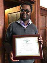 Malvern Madondo holding his Student Employee of the Year certificate
